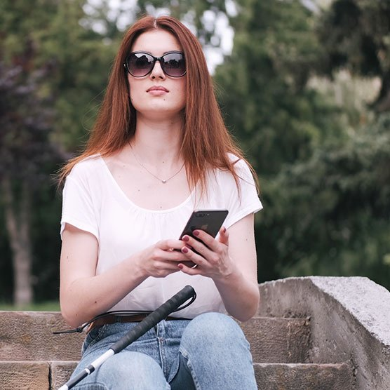 A woman sits outside holding her smartphone while her white cane leans against her leg